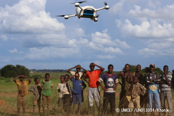 On 14 March 2016, children in Malawi look on amazed in the community demonstration of Unmanned Aerial Vehicles (UAVs or drones) flying in Lilongwe. The Ministry of Health and UNICEF launched the first 10km auto programmed flight in a trial to speed up the testing and diagnosis of HIV in infants. Malawi has a national HIV prevalence rate of 10% - still one of the highest in the world. An estimated 1 million Malawians were living with HIV in 2013 and 48,000 died from HIV-related illnesses in the same year. Whilst progress has been made, and today 90% of pregnant women know their HIV status, there is still a drop off with testing and treating babies and children. In 2014, around 10,000 children in Malawi died from HIV-related diseases and less than half of all children were on treatment. Samples are currently transported by road, either by motorbike or local authority ambulances. Various factors including the high cost of diesel fuel, poor state of roads and limited distribution schedules have resulted in extreme delays in lab sample transport, constituting a significant impediment for the scaling up of paediatric ART's effectiveness. In March 2016, the Government of Malawi and UNICEF have started testing the use of Unmanned Aerial Vehicles (UAVs or drones) to explore cost effective ways of reducing waiting times for HIV testing of infants. The test, which is using simulated samples, will have the potential to cut waiting times dramatically, and if successful will be integrated into the health system alongside others mechanisms such as road transport and SMS. The first successful test flight completed the 10km route unhindered travelling from a community health centre to the Kamuzu Central Hospital laboratory. Local residents gathered in amazement as the vehicle took off and flew away in the direction of the hospital. The test flights which are assessing viability including cost and safety, will continue until Friday 18th March. The UAV flights are suppo